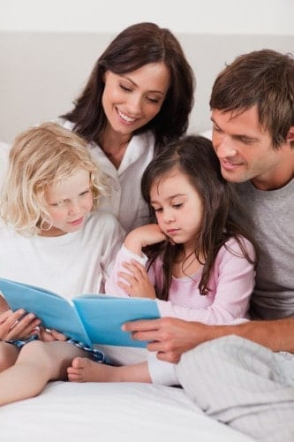 Portrait of a family reading a book in a bedroom
